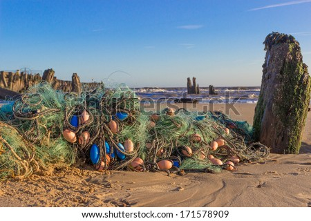 After a storm, some fishing nets have been thrown up on the beach at Walberswick, Suffolk, UK - stock photo