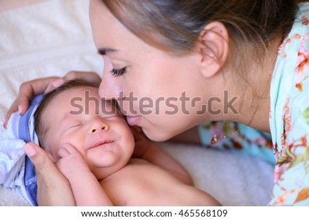 After childbirth newborn baby sleeping in a bed with mammy