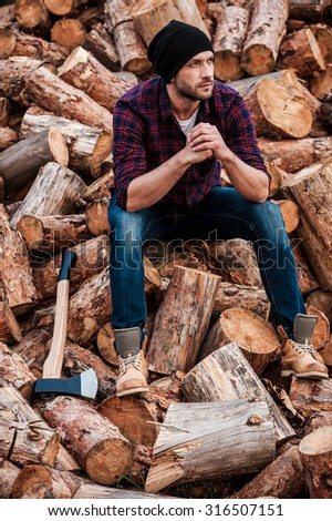 After hard physical work. Full length of thoughtful young forester keeping hands clasped and looking away while sitting on logs - stock photo
