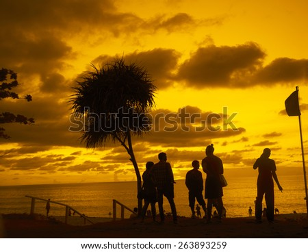 After Party young adult people on hot evening summer coast beach on yellow or orange dramatic sunset sky with clouds  background Gays talking at mobile cell phone Kids swim in ocean against horizon  - stock photo