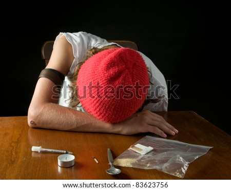 after shooting heroin: teen boy in stupor, with drug paraphernalia, and belt still around his arm.  Heroin usage still a serious problems among teens. - stock photo