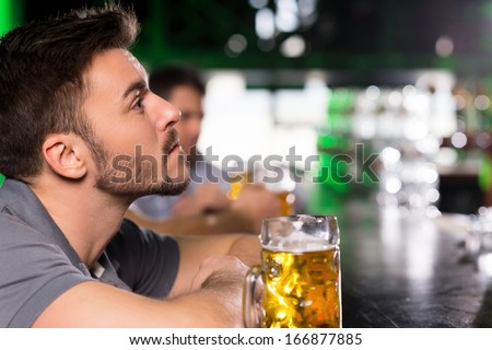 After the hard working day. Side view of thoughtful young man drinking beer in bar - stock photo