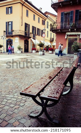 After the rain. Wet bench in Menaggio, Lake Como, Italy. Vintage, old city, European, travel and vacation concept. - stock photo