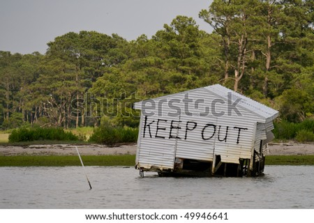 Aftermath of a flood showing a dangerous abandoned building. - stock photo