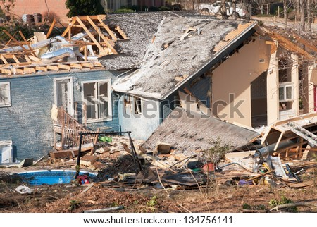 Aftermath of a tornado damaged blue wood framed house. The storm came through this residential neighborhood in March and damaged numerous houses in its path. - stock photo