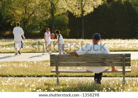 Afternoon at the park(the air is full of floating dandelion seeds lit by the afternoon sun) - stock photo