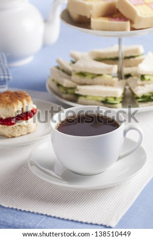 Afternoon cup of tea with cucumber sandwiches and scones in the background. - stock photo