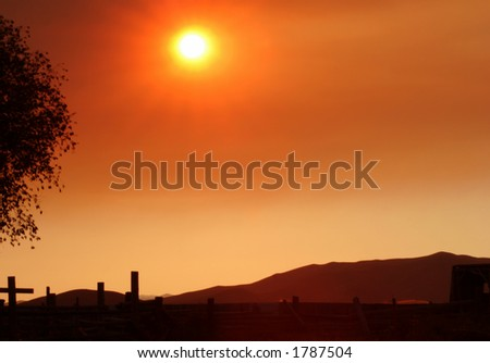 Afternoon sun filtered through smoke from forest fire - stock photo