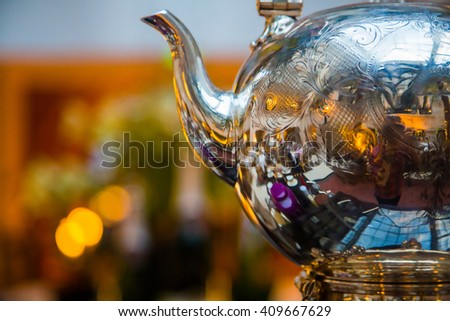Afternoon tea ceremony with a shiny tea pot on the table in London - stock photo