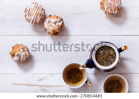 Afternoon tea with cakes on the table top view. Muffins on white  table with green tea. The Time of Tea Break.  - stock photo