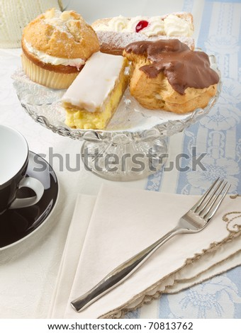 Afternoon Tea with selection of cream cakes on glass cake stand, - stock photo