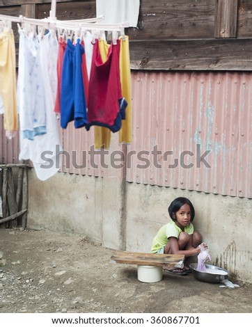 AGADA, PHILIPPINES - MARCH 23, 2012: Girl washing clothes in the small village in Philippines. About 12 per cent of Philippines children between the ages of five and 14 are forced to work.  - stock photo
