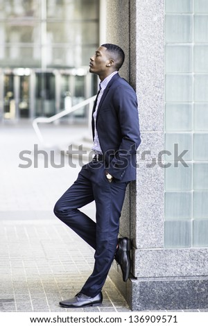 Against a wall a young black guy is deeply thinking outside - stock photo