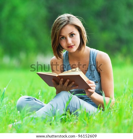 against background of green meadow (grass meadow) sat young, charming girl - student reads book