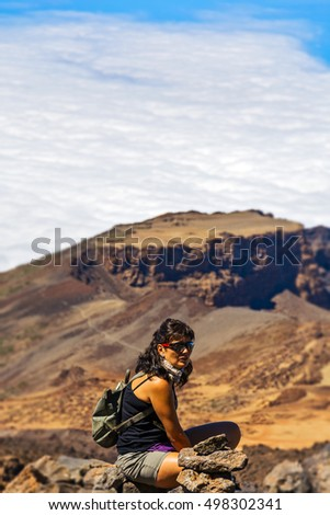 Against the background of mountains and clouds sits a woman in shorts with a backpack