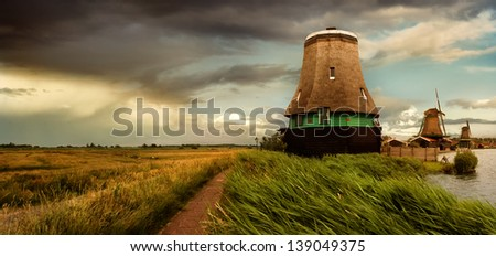 Against the background of storm clouds around the lake are old Windmills - stock photo