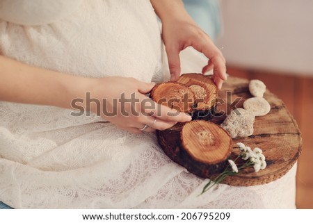 against the background of the abdomen of pregnant woman holding a wooden crafts and stones