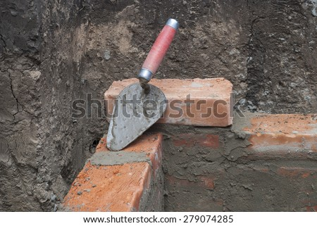 against the background of the brickwork is trowel - stock photo