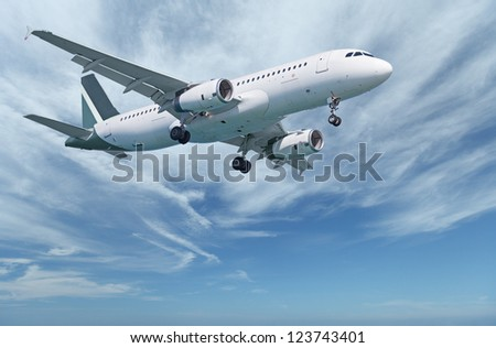 Against the background of the cloudy sky flying commercial aircraft