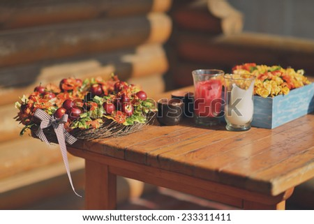 against the background of the house wooden table with a decorative basket with red apples - stock photo