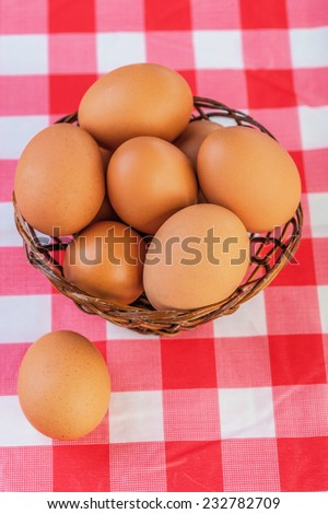 against the background of the table with checkered red tablecloth, brown eggs in wicker basket