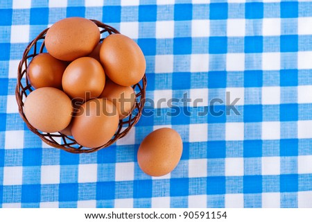 against the background of the table with checkered tablecloth, brown eggs in wicker basket