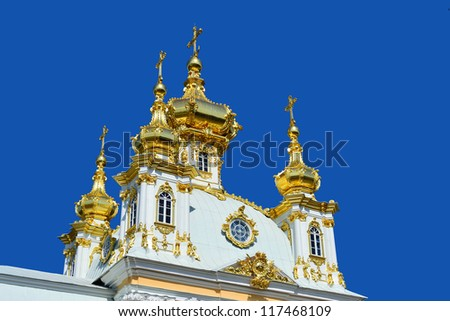 Against the blue summer sky gold domes of an orthodox temple in Peterhof - stock photo