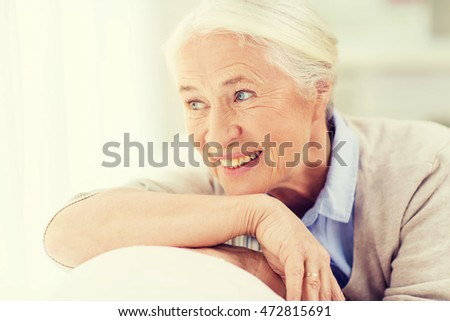 age and people concept - happy smiling senior woman face at home