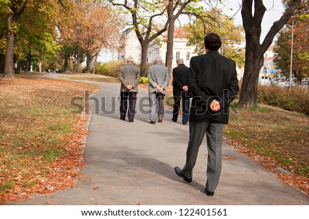 age difference, young man in the suit walking behind seniors,with both hands on his back,thinking about ,passing of life time - stock photo