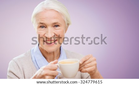 age, drink and people concept - happy smiling senior woman with cup of coffee over violet background - stock photo