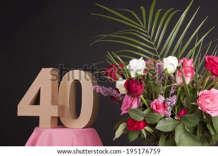 Age in figures next to a bouquet of flowers on a black background