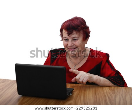 Age is no obstacle to learn modern technologies - senior woman in red dress sits behind table, smiles and points finger to laptop screen. Portrait isolated on white background - stock photo