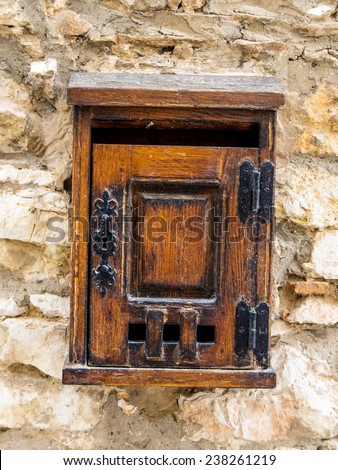 age letter box made of wood on a house wall - stock photo