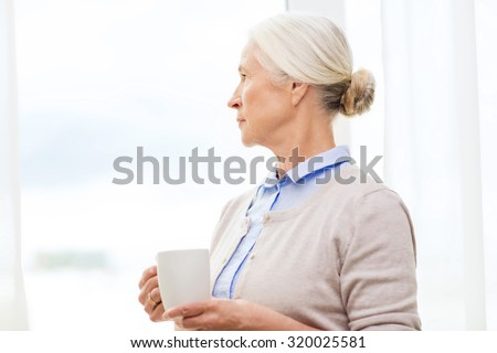 age, loneliness and people concept - lonely senior woman with cup of tea or coffee looking through window at home - stock photo