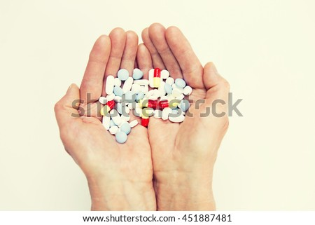age, medicine, health care and people concept - close up of senior woman cupped hands with pills at home or hospital - stock photo