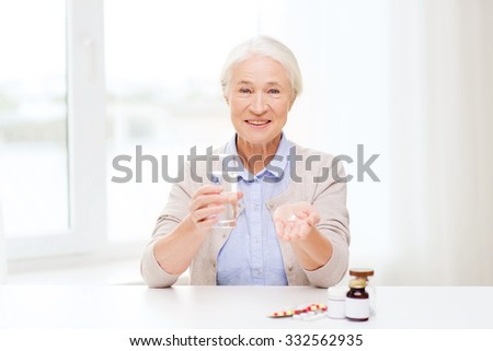 age, medicine, health care and people concept - happy senior woman with pills and glass of water at home - stock photo
