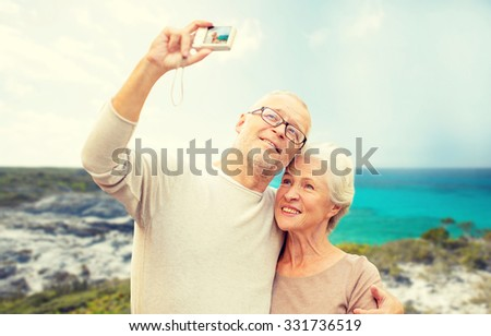 age, tourism, travel, technology and people concept - senior couple with camera taking selfie on street over beach background - stock photo