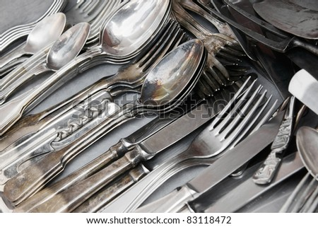 Aged and tarnished silver cutlery for sale at the flea market. - stock photo