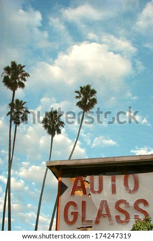 aged and worn photo of auto glass sign with palm trees - stock photo