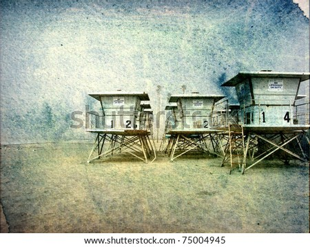 aged and worn photo of lifeguard towers on beach - stock photo