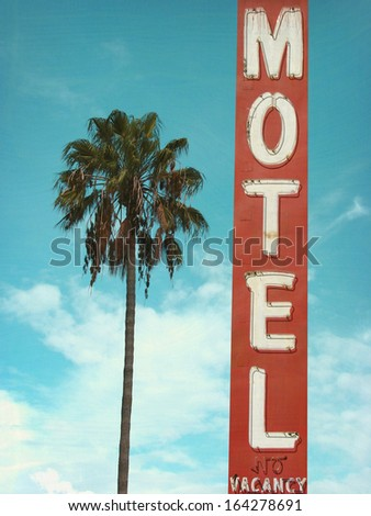 aged and worn retro photo of neon motel sign and palm tree                               - stock photo
