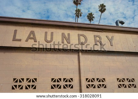 aged and worn vintage laundry sign with palm trees - stock photo