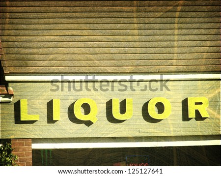aged and worn vintage liquor store sign - stock photo