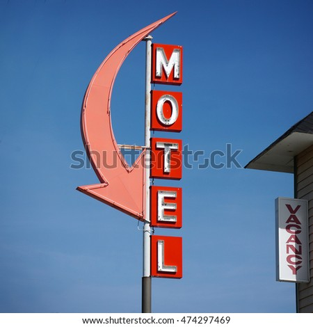 aged and worn vintage neon motel sign with arrow