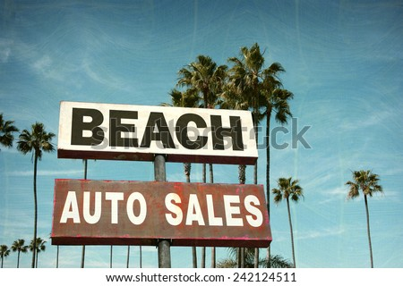 aged and worn vintage photo of auto sales sign on beach - stock photo