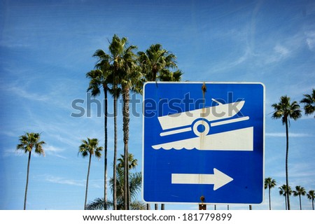 aged and worn vintage photo of boat launch sign with palm trees                                - stock photo