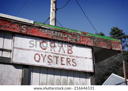 aged and worn vintage photo of crab and oyster sign