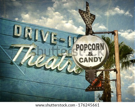 aged and worn vintage photo of drive in movies sign with popcorn and candy advertisement                              - stock photo