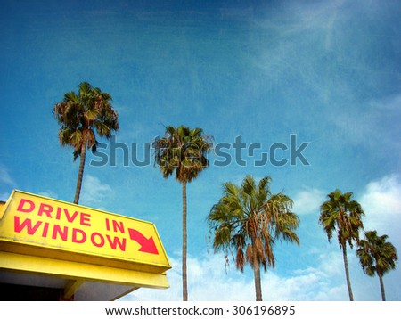 aged and worn vintage photo of drive in window sign and palm trees                                - stock photo
