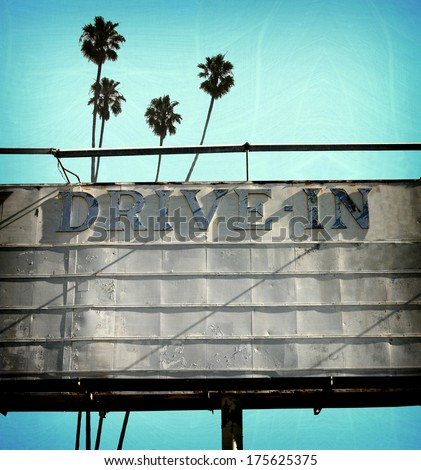 aged and worn vintage photo of drive movies billboard and pal trees - stock photo